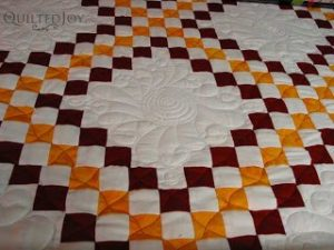 Curly Feathered Wreaths on Irish Chain quilt, quilted by Angela Huffman