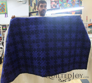 Joel custom quilted this dark blue sawtooth quilt at the Quilted Joy showroom