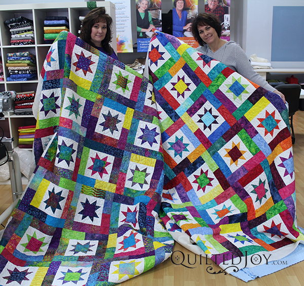 Paula and Lark showoff their Sawtooth quilts after their longarm quilting machine rental at the Quilted Joy showroom.