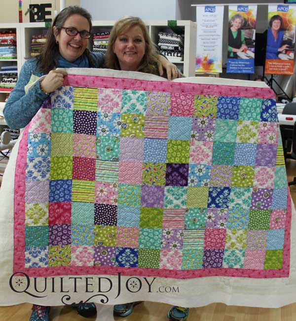 Kim's bright and colorful layer cake quilt. Quilted with the hearts and flowers design board.