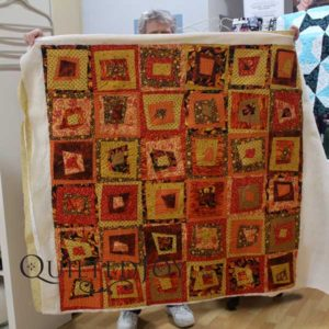 Angela Huffman at Quilted Joy assisted LuAnn on quilting this wonky log cabin quilt.