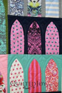 Longarm quilter Angela Huffman carved out some of the smaller arches with a simple continuous line design.