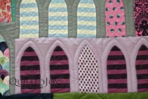 Longarm quilter Angela Huffman filled the simpler arches with motifs such as a stacked curls and ribbon candy