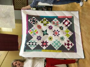 Bethanne Nemesh shows one of her sample quilts for the Sampler Quilt Smackdown Class
