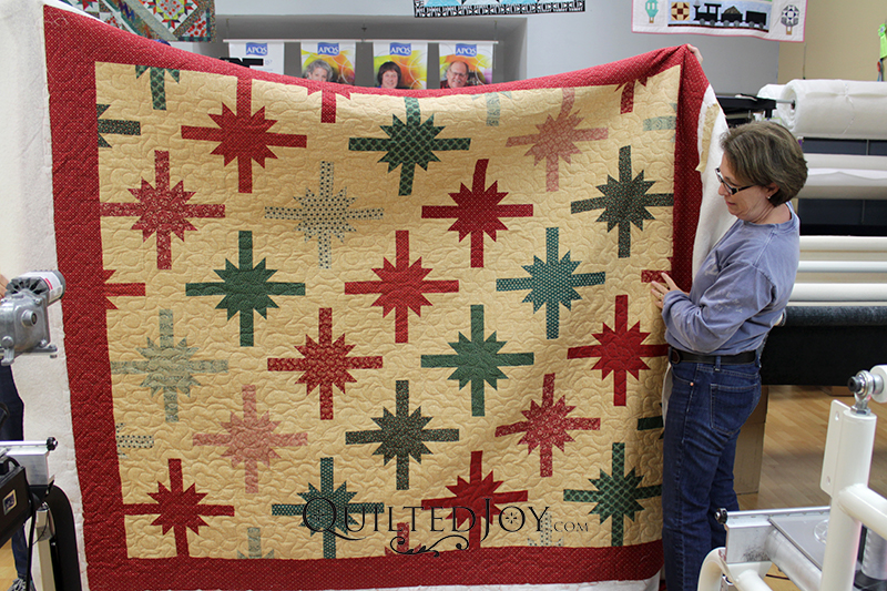 Nancy's Christmas quilt looks like bows on a present! She quilted this with the Bell Blossom pantograph because it reminded her of poinsettias.
