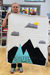 What a beautiful mountain-scape wallhanging quilt! Sue free motion quilted this with simple lines to mimic air and clouds flowing through the air.