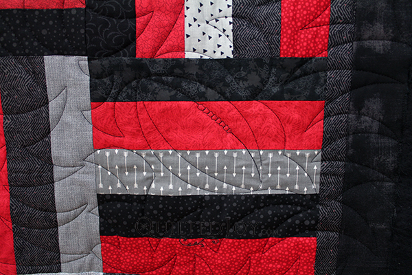 Karen made this Rail Fence quilt for her son and she has lots of hidden meanings in it's design. It's red, black, and grey, because he's an avid UofL supporter and it's quilted with footballs because he played while growing up.