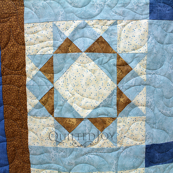 Jodi made a beautiful blue, green, and gold sampler quilt and asked me to quilt it for her. We looked at her fabrics for inspiration to choose the perfect edge to edge design.