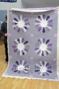 Valerie's modern Dresden quilt is gorgeous! She free motion quilted this on a longarm quilting machine at Quilted Joy.