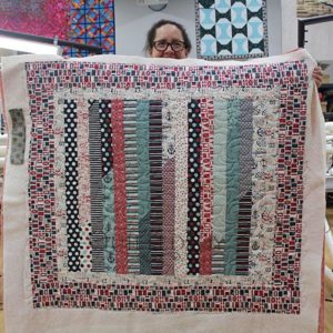 Kathleen displays her Jelly Roll Race Quilt with red, white, and blue nautical themed fabrics at Quilted Joy after her longarm quilting machine rental