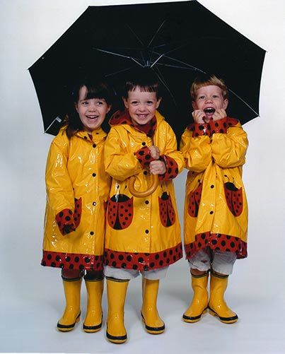 Angela Huffman's three kids in raincoats, rain boots, and an umbrella