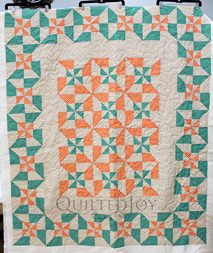 Vintage inspired pinwheel block variation quilt in cream, green, and orange colors
