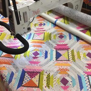 Millie Longarm Machine with Intelliquilter quilting a pineapple block with bright colorful fabrics