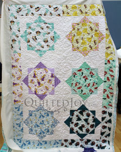 Colleen shows off her Disney Princesses Quilt after renting a longarm machine at Quilted Joy