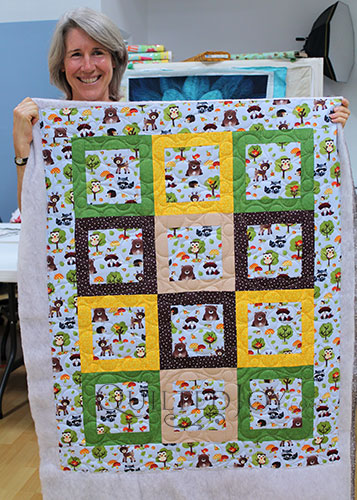 Joyce's Woodland Creatures Focal Fabric Quilt after a longarm machine rental at Quilted Joy