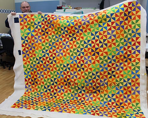 Dennis shows off his bright primary colored Pinwheel Block Quilt