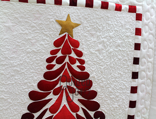 Falicia custom quilted her Christmas tree quilt using a longarm machine at Quilted Joy