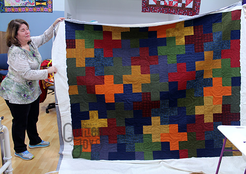 Anna Maria shows off a plus sign flannel quilt after quilting it on a longarm machine at Quilted Joy