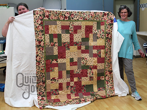Annette shows off her quilting after renting a longarm quilting machine at Quilted Joy