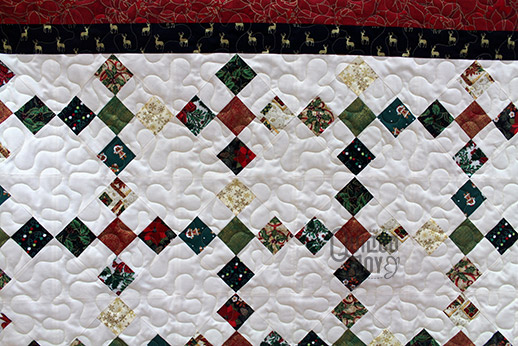 Carol's Christmas themed Irish Chain quilt after quilting it at Quilted Joy