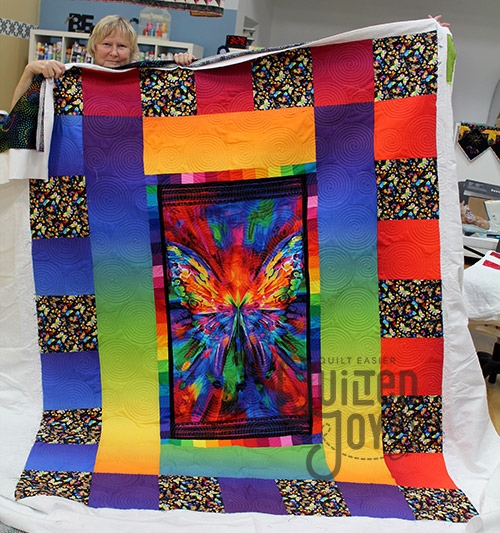 Claudia shows offer her butterfly rainbow quilt after quilting it on a longarm machine at Quilted joy