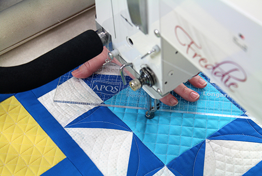 Using a ruler to quilt a crosshatching quilting design on a longarm quilting machine