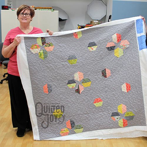 Peggy shows off her applique quilt after renting a longarm quilting machine at Quilted Joy