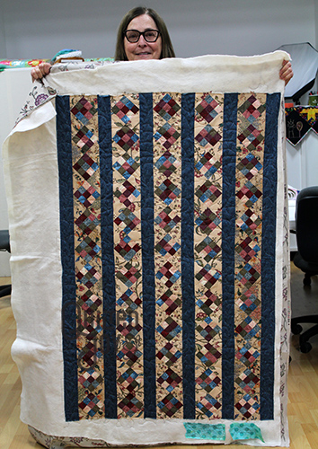 Rita quilted her nine patch and stripes quilt on a longarm machine at Quilted Joy