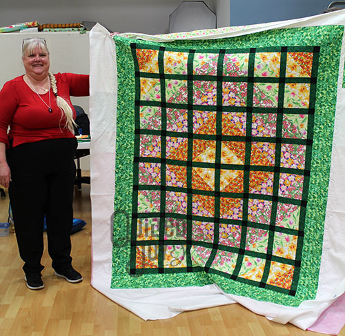 Betty shows off her latticework quilt after quilting it on a longarm machine at Quilted Joy