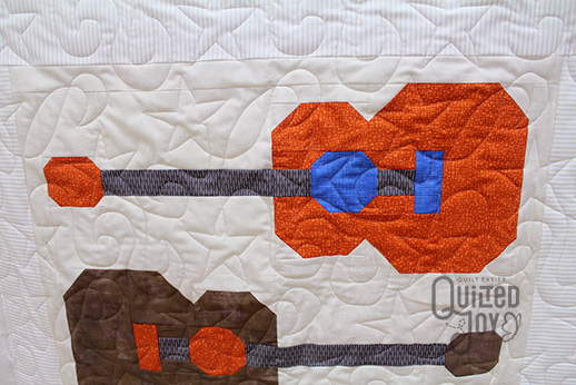 Colleen shows off her guitars quilt after quilting it on a longarm at Quilted Joy