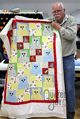 John shows off his teddy bear quilt after renting time on a longarm quilting machine