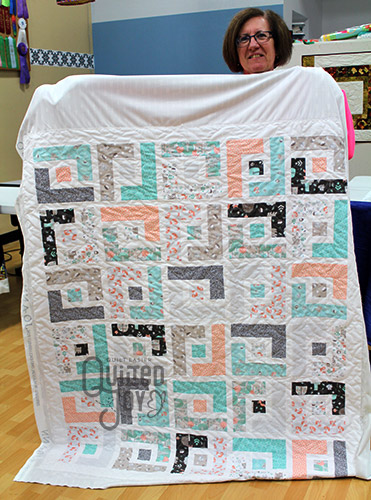 Judy shows off the Log Cabin quilt she quilted at Quilted Joy