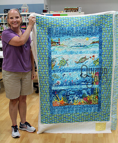 Jana shows off her sea life panel quilt after renting an APQS longarm quilting machine at Quilted Joy