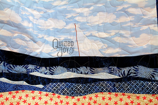 Karen shows off her appliqued beach quilt after longarm quilting it at Quilted Joy