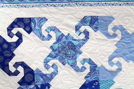Karen shows off her snail trail quilt after longarm quilting it at Quilted Joy