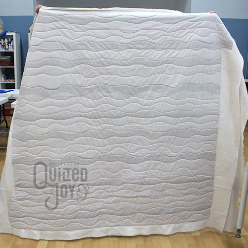 Peggy's grey waves quilt after quilting it on a longarm quilting machine at Quilted Joy