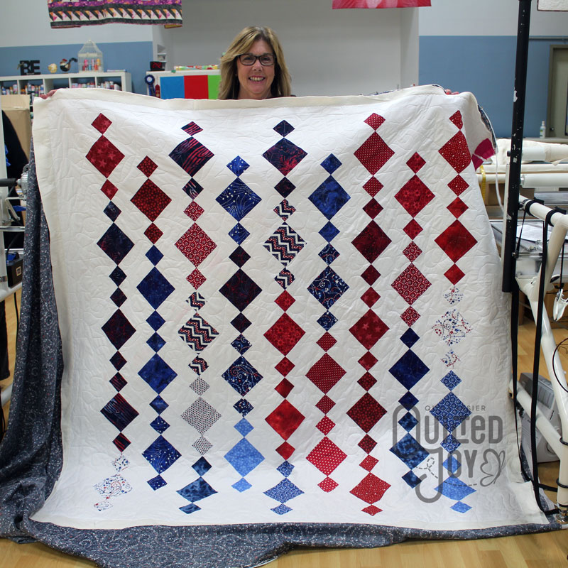 Cheri's patriotic quilt after longarm quilting it at Quilted Joy